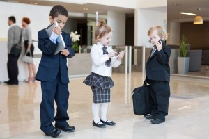Children with communication devices in business clothing